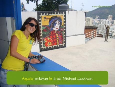 Pronomes Demonstrativos em Português. Aquela estátua lá é do Michael Jackson.