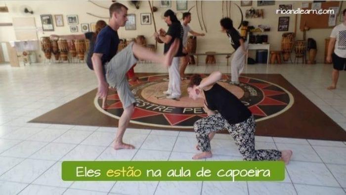 Verbo Estar no Presente do Indicativo no Português. Exemplo: Eles estão na aula de capoeira.
