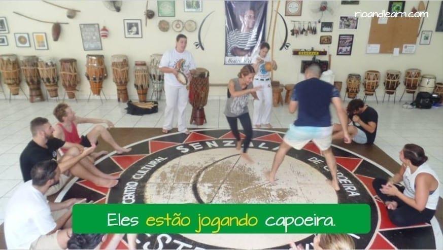 Present continuous tense in portuguese. Eles estão jogando capoeira.