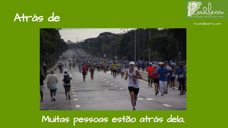 Preposiciones de Lugar en Portugués. Ejemplo con Atrás de: Muitas pessoas estão atrás dela.