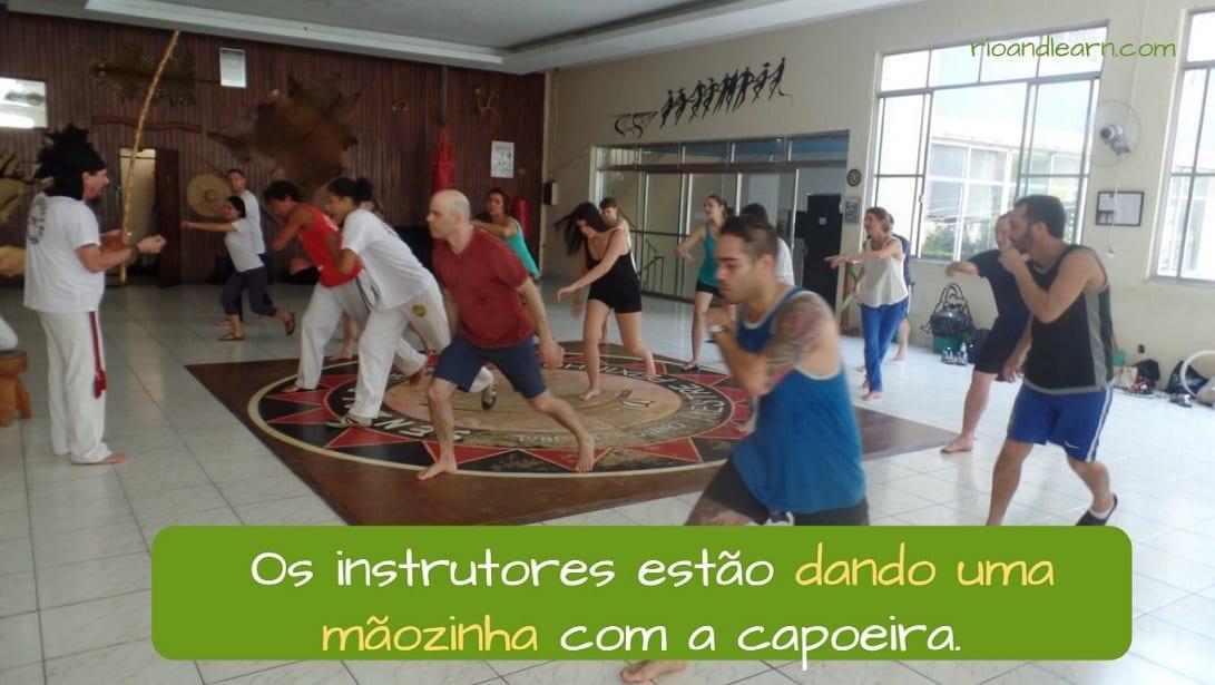 Expressões Idiomáticas em Português. Os instrutores estão dando uma mãozinha com a capoeira.