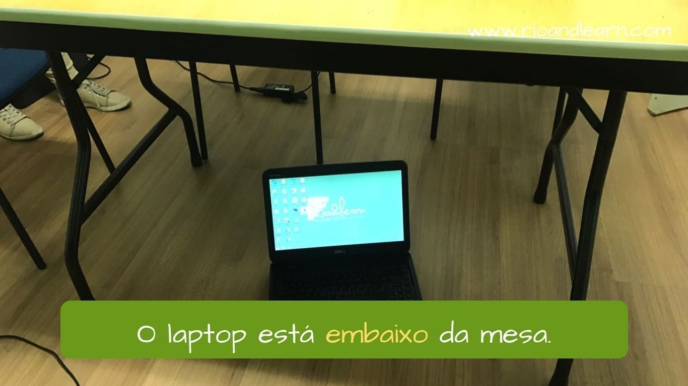 What does baixo mean in Portuguese. O tênis laptop embaixo da mesa.