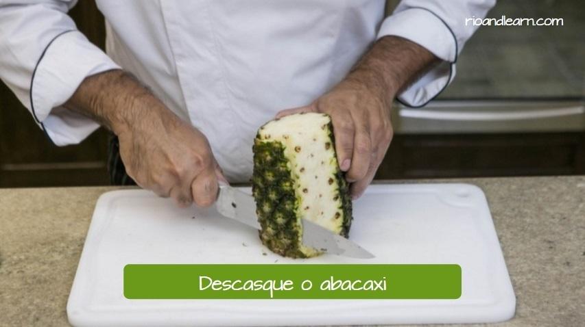 Primer paso para una receta de zumo de piña en portugués: Descasque o abacaxi (Traducción: pela la piña).