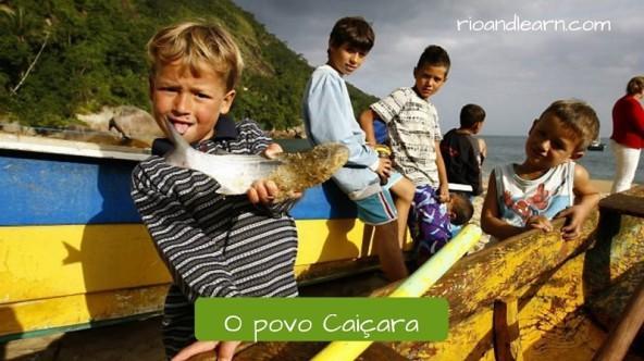 El pueblo caiçara. Cinco niños caiçaras muestran un pez que pescaron en su barco de pesca. El barco tiene los colores verde y amarillo y aparece un morro característico de la región al fondo. O Povo Caiçara. Traducción: El pueblo Caiçara.
