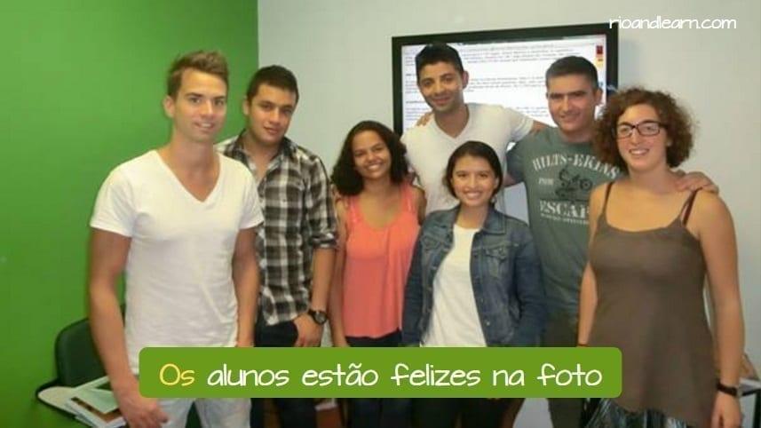 Exemplo com artigos definidos em Português: Os alunos estão felizes na foto.