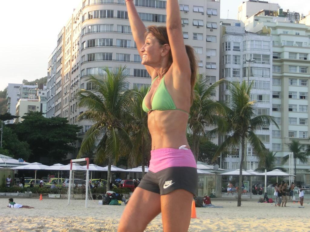 Português e volleyball. Healthy woman playing volleyball at Copacabana beach