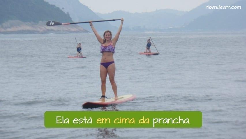 Ela está em cima da prancha. Portuguese Prepositions.