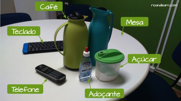 Exercises with Prepositions of Place in Portuguese. Office vocabulary in Portuguese: Keyboard, phone, table, sugar, coffee, sweetener.