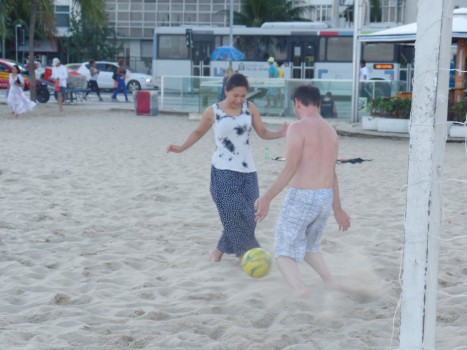 Japonese students paying beach soccer.