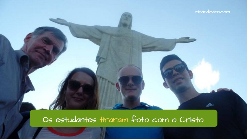 Verb Tirar. To Take. O estudantes tiram foto com o Cristo. Students took a picture with the Cristo. Christ the Redeemer.