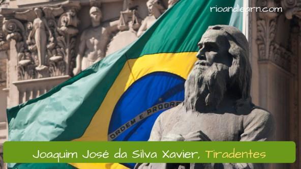História de Tiradentes. Joaquim José da Silva Xavier, Tiradentes. Estátua de Joaquim José da Silva Xavier, mais conhecido como Tiradentes, com a bandeira do Brasil ao fundo.
