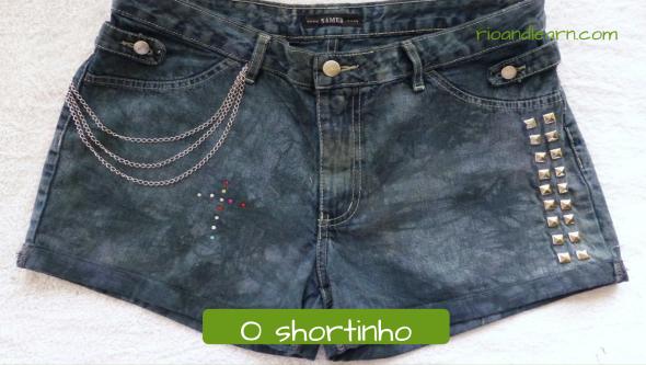 Roupas femininas comuns no Brasil: O shortinho. Shortinho jeans curto com detalhes em metal e miçanga e correntinha.