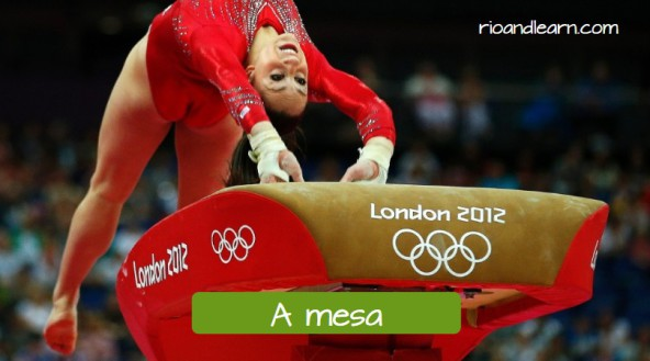 Equipments used for artistic gymnastics in the olympic games. The vault: A mesa. Female gymnast in red uniform jumping over the vault.