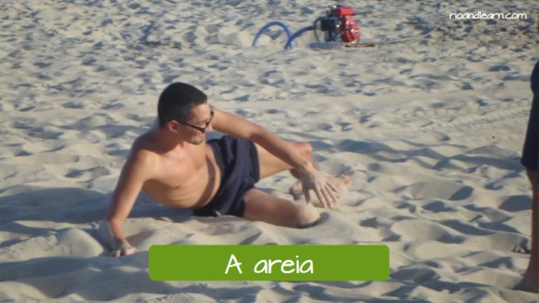 The sand: A areia. Portuguese language student laying on the sand of Copacabana Beach.