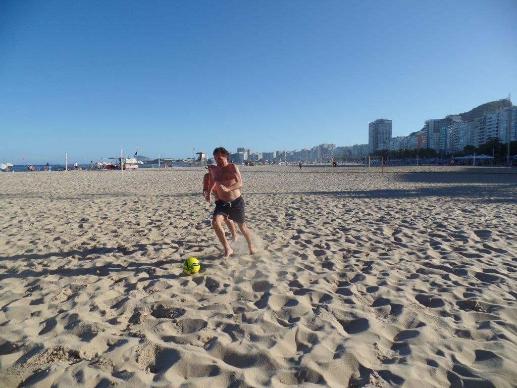 Futebol em Copacabana. Estudantes jogando futebol na praia de Copacabana.