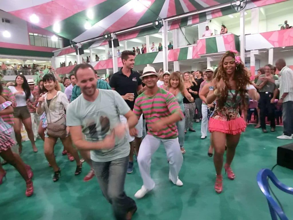 Visita a Escola de Samba. Todos sambando. Gringos sambando com passistas da Mangueira.