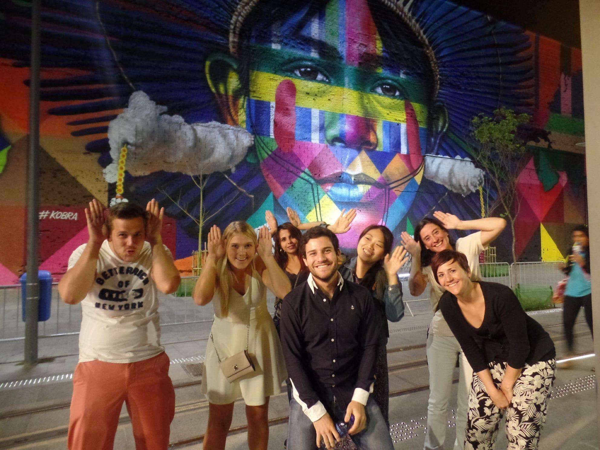 Estudiantes de la Rio & Learn bromeando en el Porto Maravilha en Río de Janeiro con un graffiti gigante detrás.