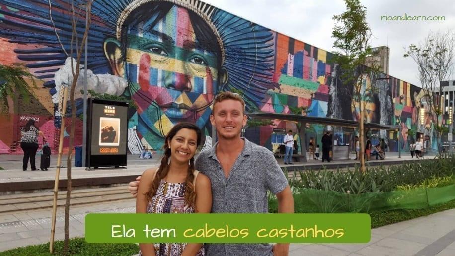 Describe someone in Portuguese. Ela tem cabelos castanhos.