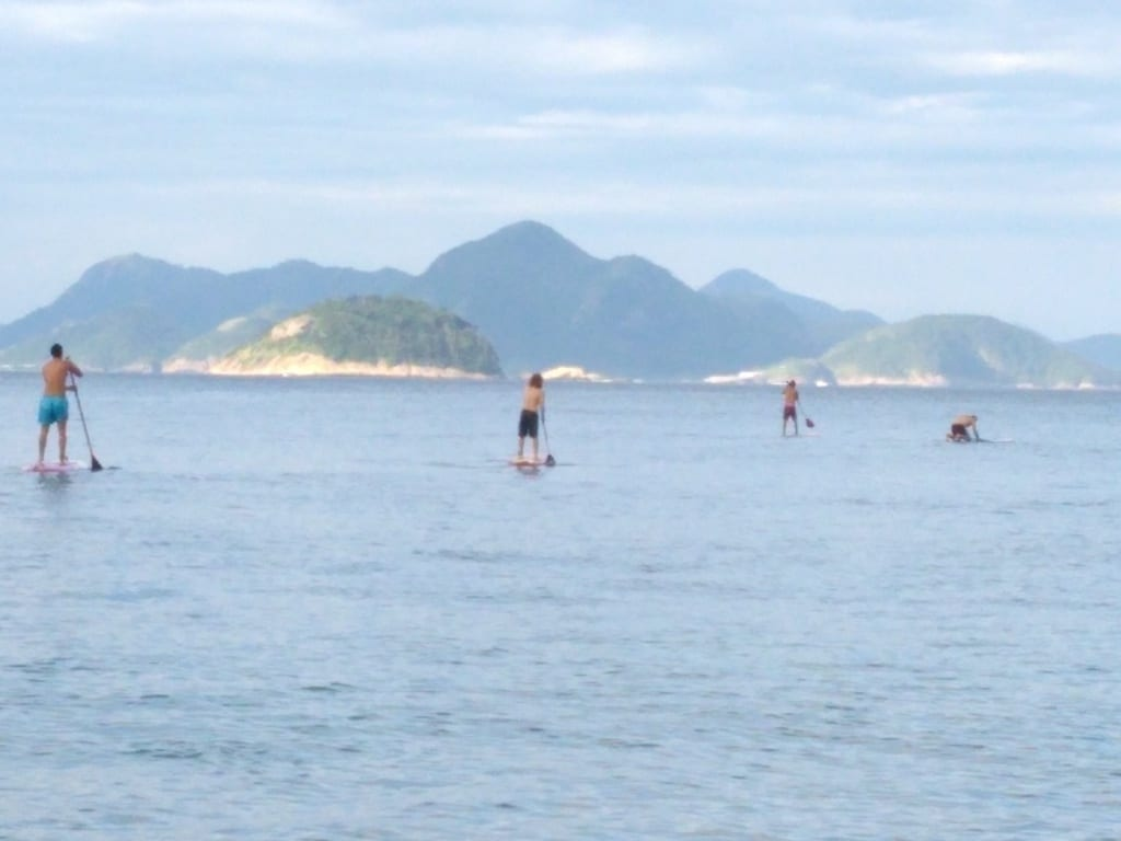 Foreigners doing paddle surf.