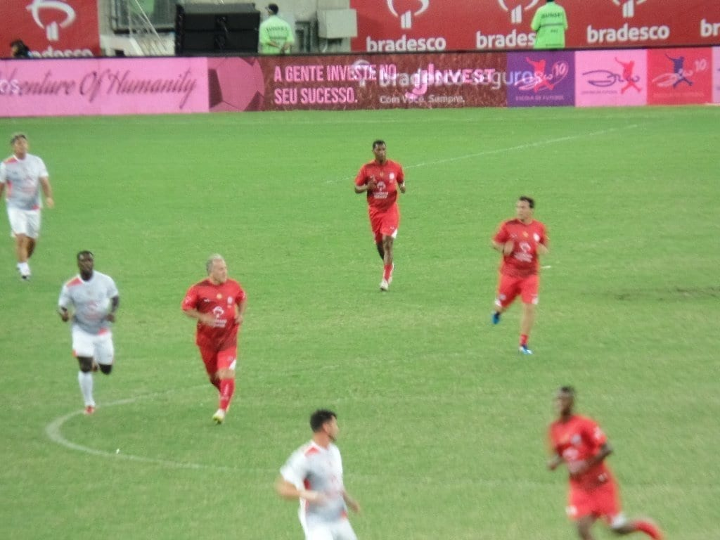 Zico playing soccer. Zico benevolent game. Red team against white team. Red against White. Four players in red. Soccer field. soccer game.
