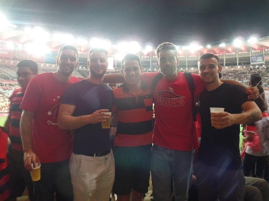 Estudiantes en el Maracaná bebiendo cerveza con las luces del estadio de fondo.
