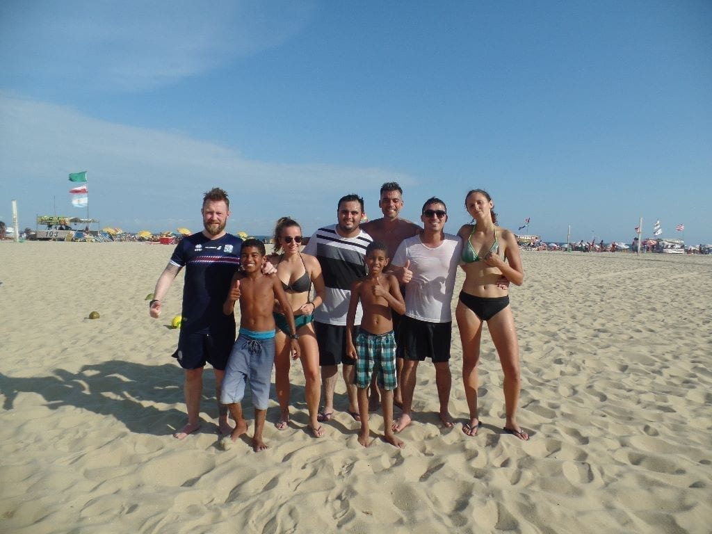 little soccer game. six foreign students of Portuguese plus two kids in the sands of Copacabana posing for the picture. Clear sky.