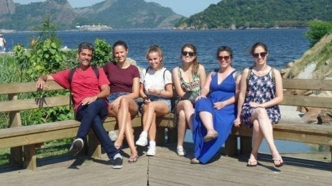 RioLIVE! Six people on a bench. One boy and five girls. Niterói view from Rio. Botafogo Cove