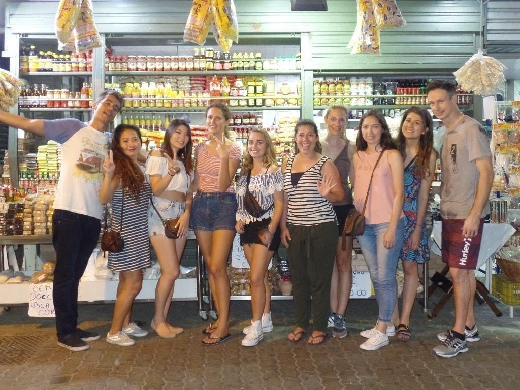 Diez estudiantes extranjeros en feria de San Cristóbal en frente de productos típicamente nordestinos.