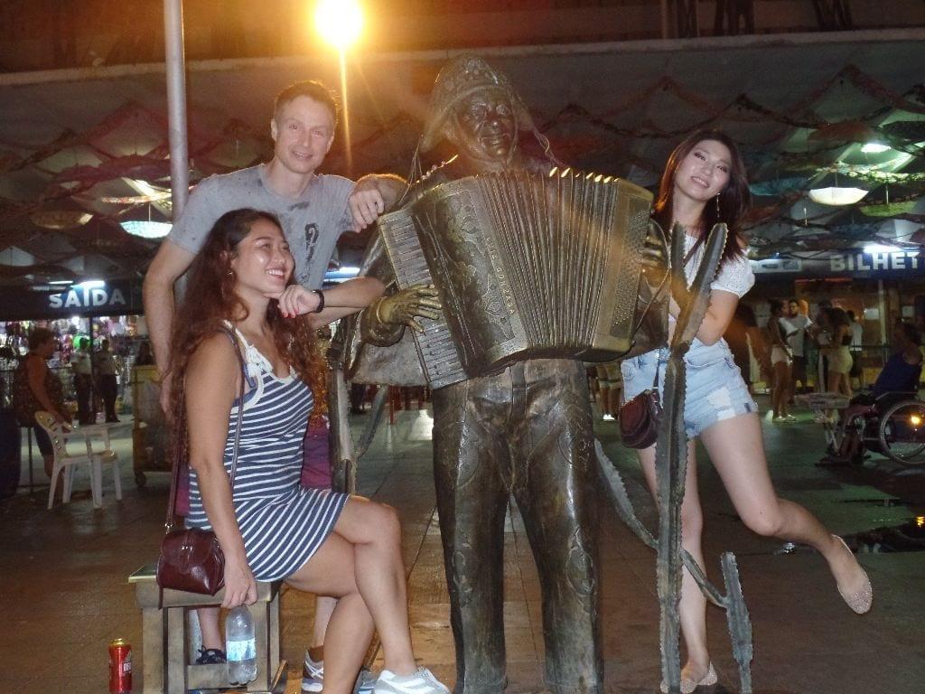 Sweet Forró. Feira de São Cristóvão. Three foreign students of Portuguese with the Luiz Gonzaga statue.