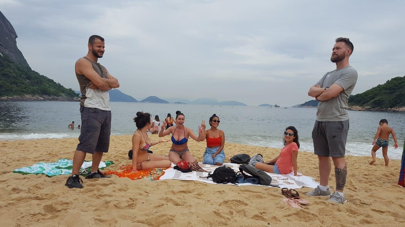Seis turistas passando um tempo na Praia Vermelha na Urca, Rio de Janeiro.