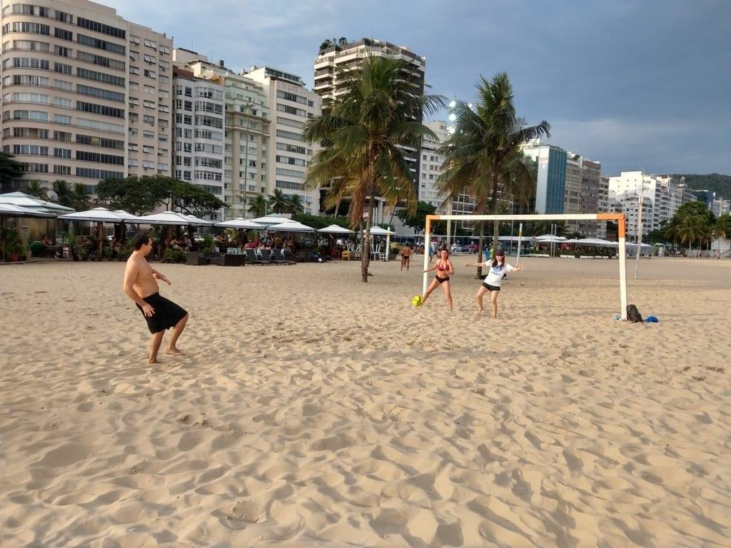 Chico chutando a una portería de fútbol con dos chicas porteras en la playa de Copacabana.