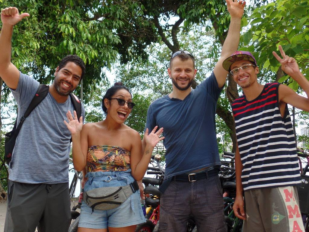 Cuatro personas felices saludando a la cámara con árboles al fondo.