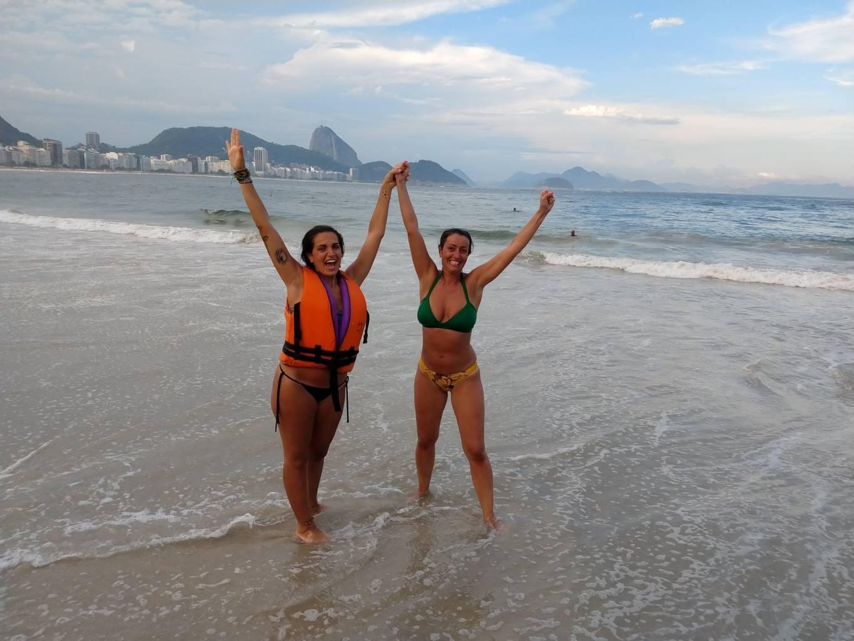 Dos chicas una con bikini brasileño y otra con chaleco salvavidas en la playa de Copacabana con el Pan de Azúcar al fondo.