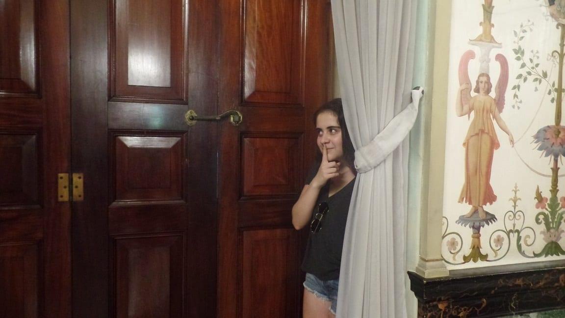 Estudiante escondida detrás de la cortina divirtiéndose en el Palácio del Catete.