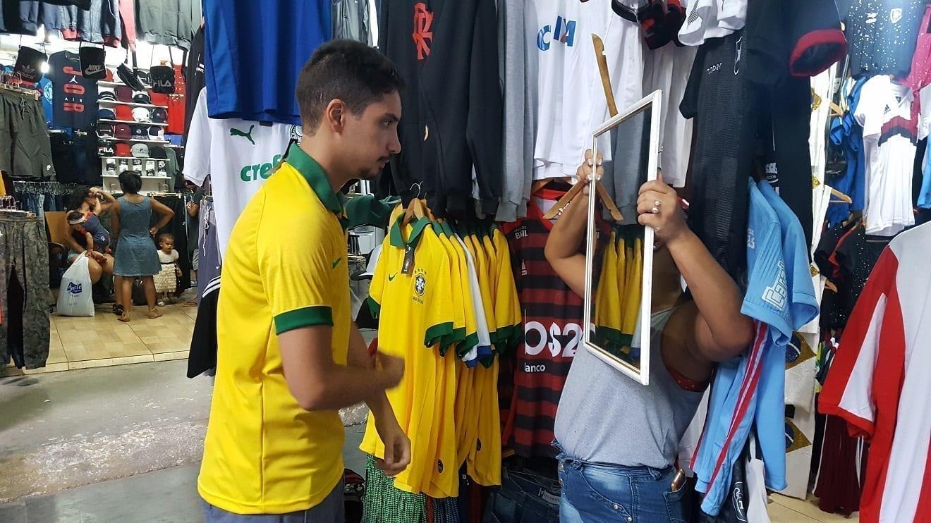 Comprando un Recuerdo en el Centro de Río de Janeiro, estudiante comprando una camisa de Brasil y mirándose en el espejo..