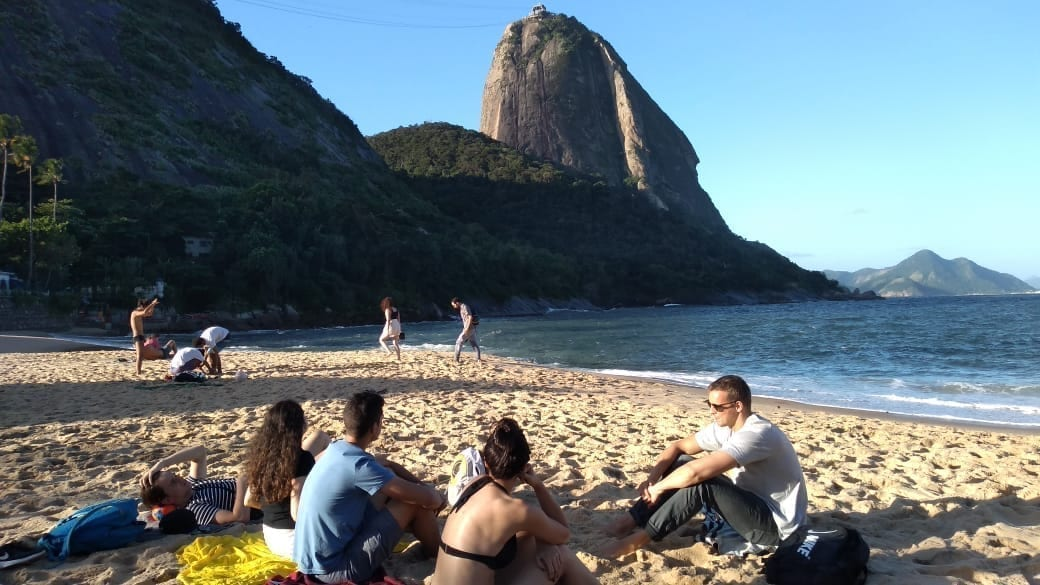 Foreign students resting at the beach and learning Portuguese at Praia Vermelha, Urca in Rio de Janeiro, Brazil