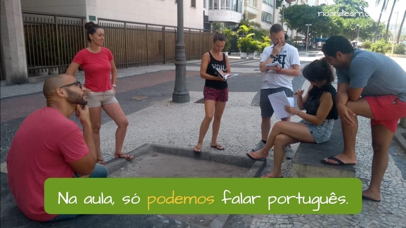 Exemplo com o verbo Poder para permissão: Na aula só podemos falar português. Estudantes falando em português.