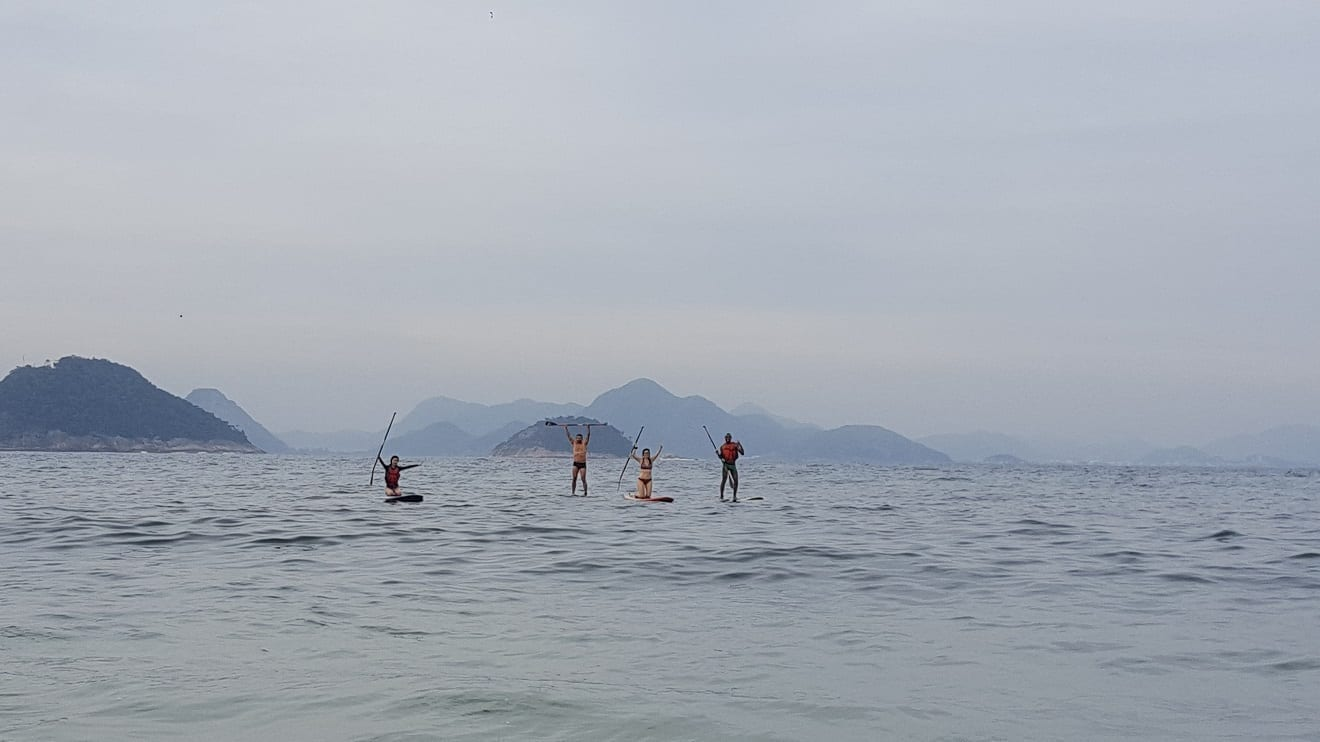 Cuatro estudiantes de Stand Up Paddle Surf en el mar de la playa de Copacabana.