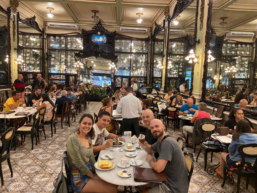 Students sitting at table drinking tea at Confeitaria Colombo