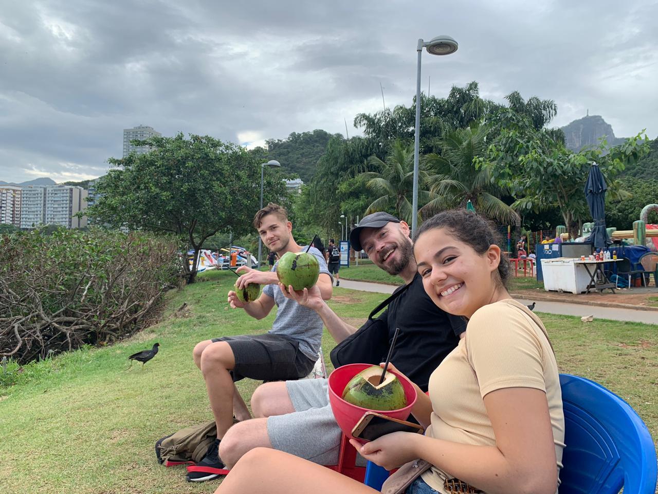 Los estudiantes bebiendo un coco junto al lago de Río de Janeiro después de pasar el día de montaña y bicicleta en la Lagoa.