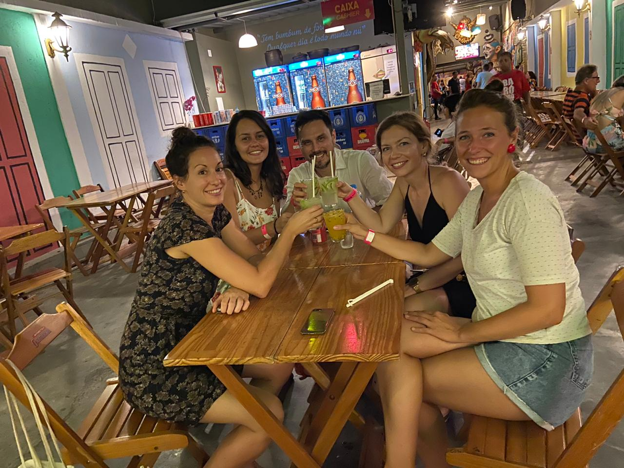 Alunos sentados na mesa bebendo caipirinhas no bar