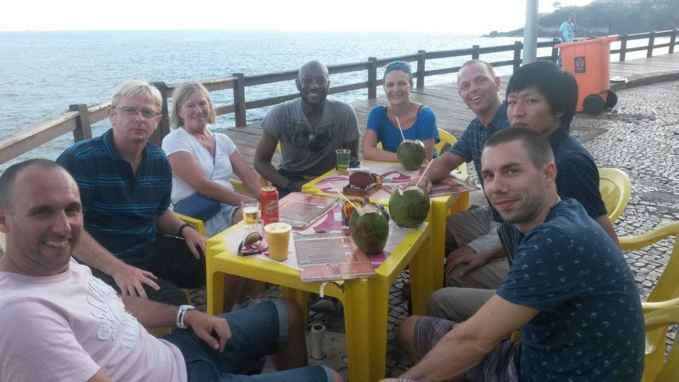Melhor Forma de Aprender Português. Imersão Real. Aprenda português no Brasil. Alunos da Rio & Learn sentam num quiosque na praia junto com membros da equipe e funcionário da escola.