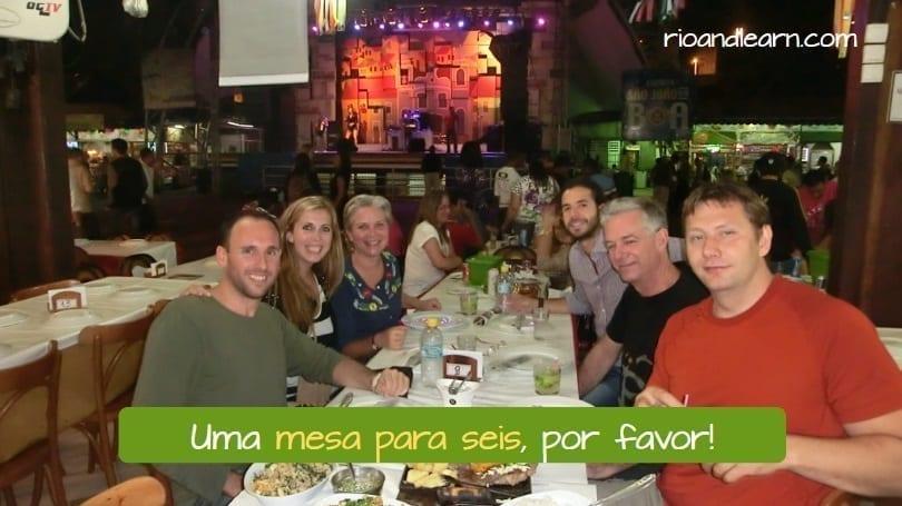 Diálogo em um Restaurante em Português. Uma mesa para seis, por favor.