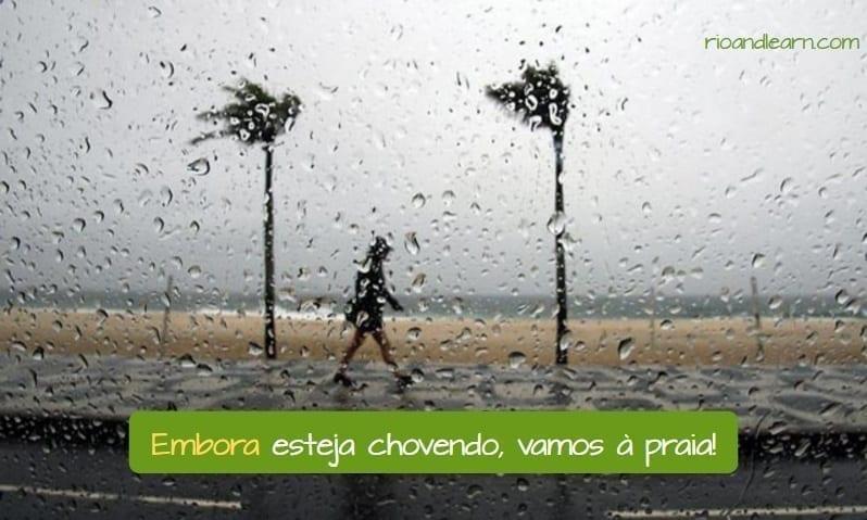 Use of Embora in Portuguese. Embora esteja chovendo, vamos à praia.