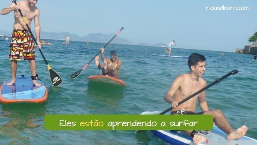 Conjugação do Verbo Estar em Português. Eles estão aprendendo a surfar. Três estudantes estrangeiros de Português fazendo aulas de Paddle Surf em Copacabana.