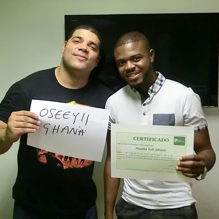 Alumno de Ghana obteniendo su certificado de portugués de Rio & Learn con la felicitación del profesor en Ghanés.