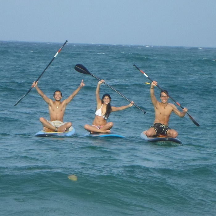 Three foreigners students in a stand up paddle surf class in Copacabana.