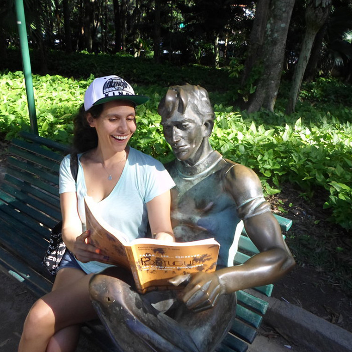 American student of Portuguese reading a book at Botanical garden.