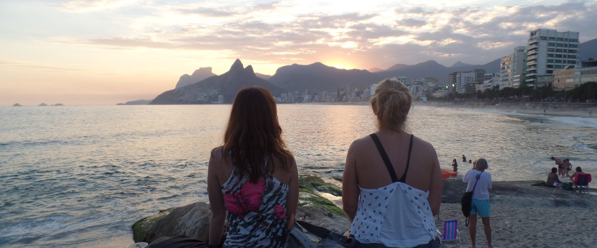 Foreigners students watching the sunset at Arpoador in Rio de Janeiro.